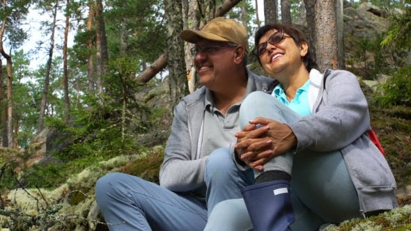 Thumbnail for Elderly Active Couple Sitting on a Rock and Admiring the Northern Forest