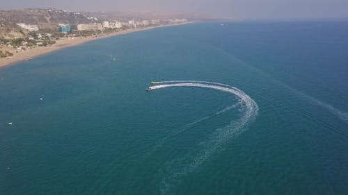 Motor Boat Tows Inflatable Circle with Vacationers