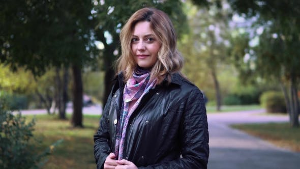 Thumbnail for Portrait of Attractive Young Woman in Autumn Park. Girl in Jacket and Scarf