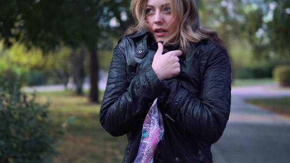 Thumbnail for the Girl Froze in the Autumn Park. Young Woman Wrapped in a Scarf and Breathes on His Hands To Warm
