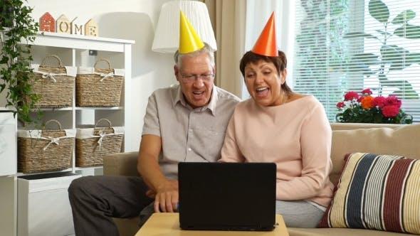 Happy Grandpa and Grandma Congratulate Their Children Happy Birthday Using Laptop Video Call