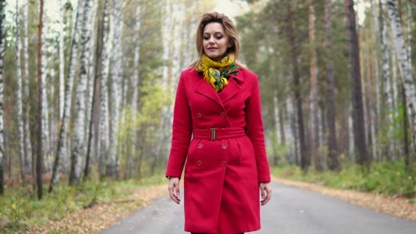 Thumbnail for Attractive Young Woman Walking in the Autumn Park. the Girl in the Red Coat and Scarf