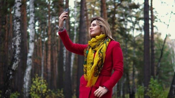Thumbnail for Young Woman in a Red Coat Walking Along an Autumn Park. Beautiful Girl Enjoying a Warm Autumn