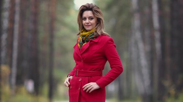 Thumbnail for Portrait of a Young Woman in an Autumn Park. Beautiful Girl in Red Coat Posing and Smiling at the