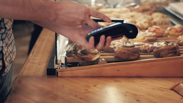 Cover Image for of Woman Making Payment Through NFC in Bakery, Cafe Restaurant, Mobile Phone Contactless Pay for