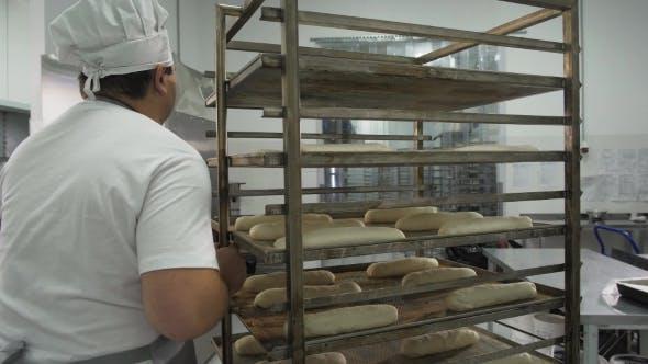 Thumbnail for Schöner Bäcker in Uniform Walk und Holding Baguettes mit Brotregalen auf dem Hintergrund an der