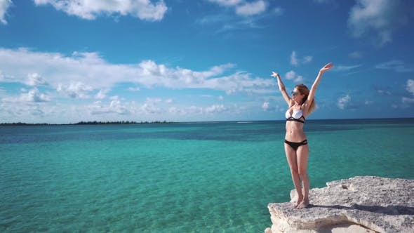 Thumbnail for A Girl Stands on a Rock Against the Azure Water of the Caribbean Sea