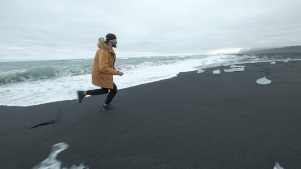 Thumbnail for Laufen Sie einen Mann in einer malerischen Naturlandschaft auf dem Laufenden Ozean in Island.