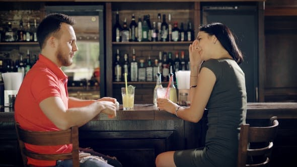 Thumbnail for Young Couple Relaxing in a Pub Sitting at Bar Counter and Drinking Beverage