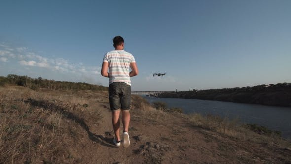 Thumbnail for Man Controlling Drone on River Shore