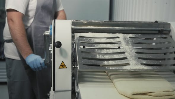 Thumbnail for Woman Working on Kitchen of Cafe and Rolling a Dough Through Machine