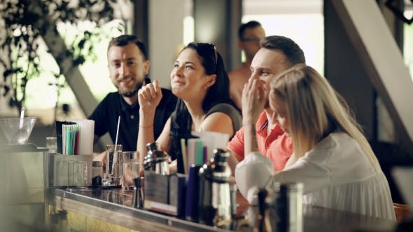 Thumbnail for Four Young People in Casual Clothes Are Talking and Laughing Sitting at Bar Counter in Summer Day