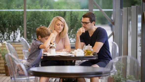 Thumbnail for Happy Family with Son Spending Time Together in Outdoor Terrace. Wife and Husband Talking While Boy
