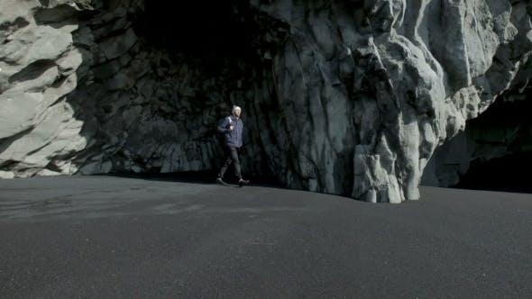 Thumbnail for Junger bärtiger Mann, der allein in einer Höhle von Island steht.