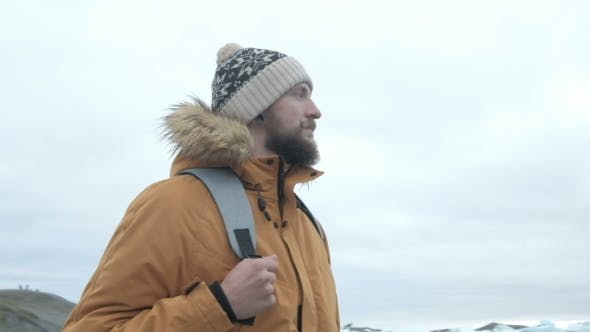 Thumbnail for Portret Bearded Man in Arctic Iceland. Dressed in a Yellow Jacket with a Backpack.