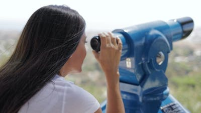 Woman Using Spyglass on City Viewpoint