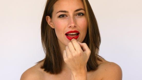 Woman Puts on Lipstick Then Kisses
