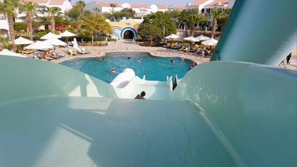 Child Is Riding a Water Slide in Water Park