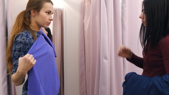 Thumbnail for Young Woman Going To Try on Dresses in Fitting Rooms with Help of Assistant