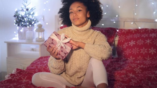 Thumbnail for Single Woman Holding Christmas Gift in Bed