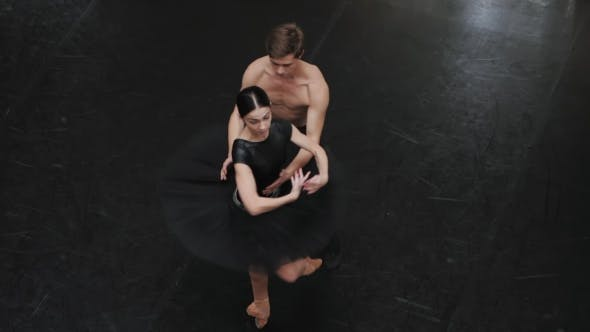 Thumbnail for Young Man Practicing in Classical Ballet with Young Beautiful Woman in Black Clothing in the Gym at