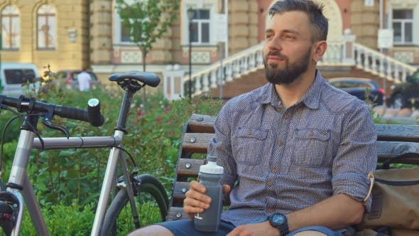 Thumbnail for Cyclist Drinks Water on the Bench
