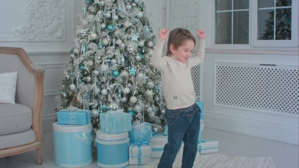 Thumbnail for Happy Little Boy Dancing Next To the Christmas Tree and Presents