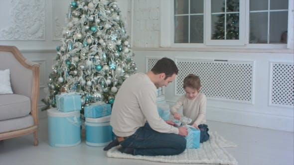 Thumbnail for Happy Father and Son Unwrapping a Present Sitting on the Floor