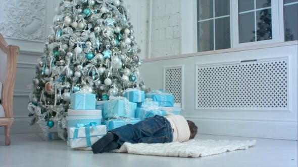 Thumbnail for Little Boy Pretending To Sleep on the Carpet Next To the Christmas Tree