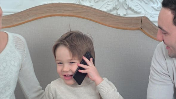 Thumbnail for Smiling Little Boy Talking on the Phone Surrounded By His Happy Family