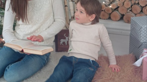 Thumbnail for Capricious Boy Listening To His Mom Reading a Book Near Christmas Tree