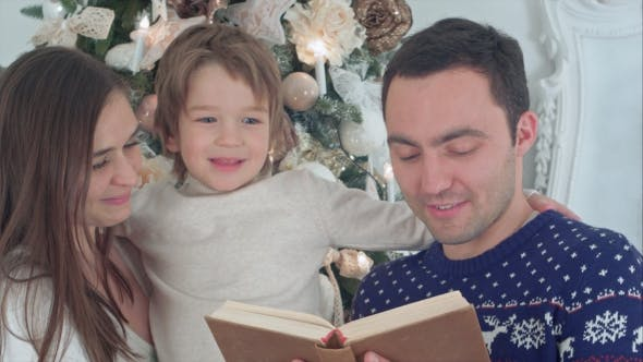 Thumbnail for Happy Family of Three Reading Together on Christmas Evening