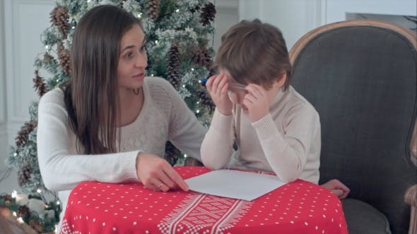Thumbnail for Young Mother Helping Her Struggling Son To Write a Letter To Santa Claus