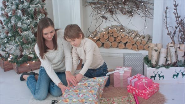 Thumbnail for Happy Mother and Her Little Son Wrapping Up Weihnachtsgeschenke zu Hause
