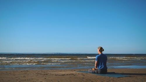 Man in Lotus Pose Meditating at the Beach