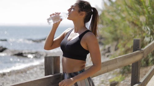 Sportswoman Drinking on Shore