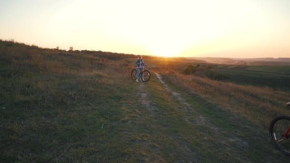 Thumbnail for Couple Is Riding a Bicycle at Sunset