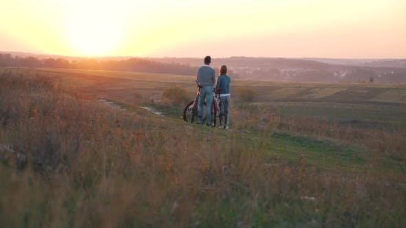 Thumbnail for A Happy Couple with Bikes at Sunset