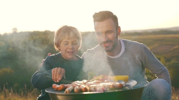 Thumbnail for Father and Son Cook Sausages on Grill
