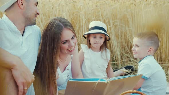 Mother Reading Funny Book to Children at Family Picnic