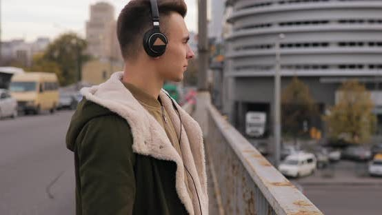 Thumbnail for Young Man Listening To Music with Headphones Walking on City Bridge