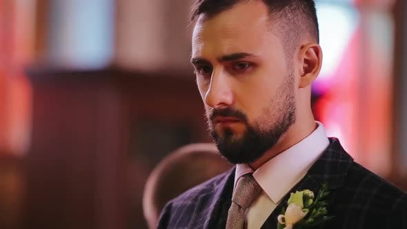 Close-up View of the Concentrated Face of a Bearded Young Bridegroom in a Stylish Suit Who Is