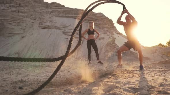 Cover Image for Athletic Man on Exercise Around the Sand Hills at Sunset Hits the Rope on the Ground and Raised the