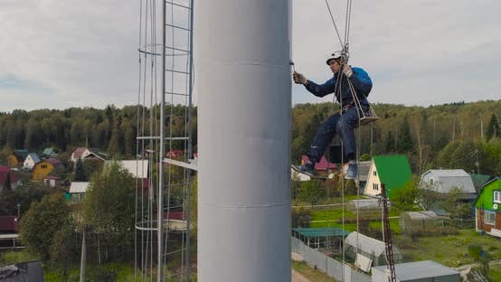 Industrial Climbers Paint the Iron Tower. Risky Job. Extreme Work