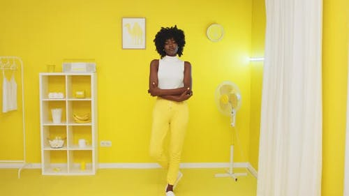 African Woman Standing In Illuminating Yellow Room