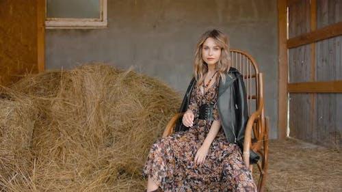 Junge Frau schwingt in einem Schaukelstuhl auf einer Ranch