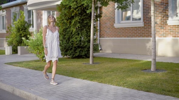 Thumbnail for Charming Cheerful Woman in Casual Dress Walking Along Sidewalk and Looking at Camera
