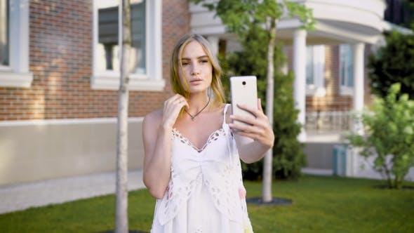 Thumbnail for junge sinnliche Mädchen in weiß nehmen selfie während posing allein bei Sommer Straße