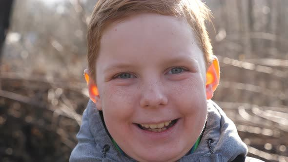 Thumbnail for Happy Joyful Red-haired Boy Looking Into Camera and Laughing Outdoor. Close Up Emotions of Little