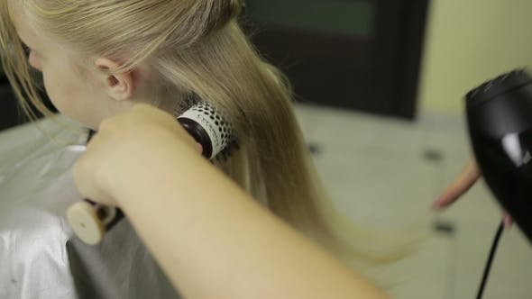 Hairdresser Drying Hair with Hair Dryer and Brush